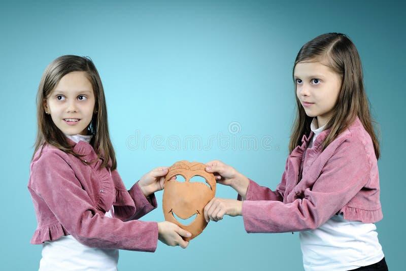 Soeurs jumelles blanches affichant le masque fabriqué à la main photographie stock libre de droits