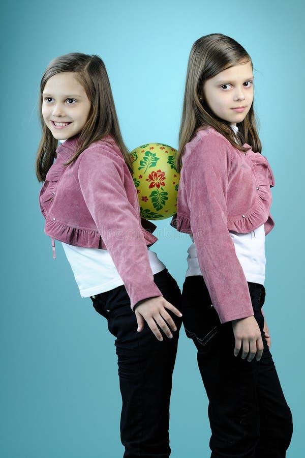 Soeurs jumelles blanches ayant l'amusement avec la bille photo stock