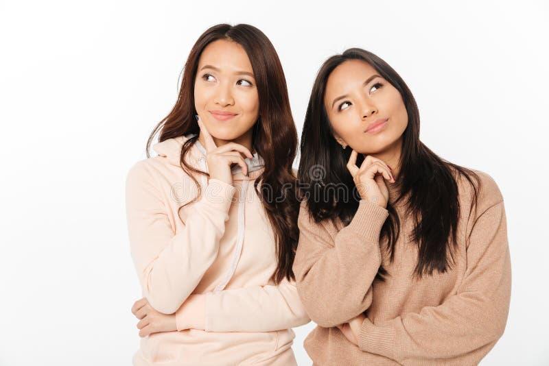 Soeurs positives réfléchies asiatiques de dames Regard de côté photographie stock
