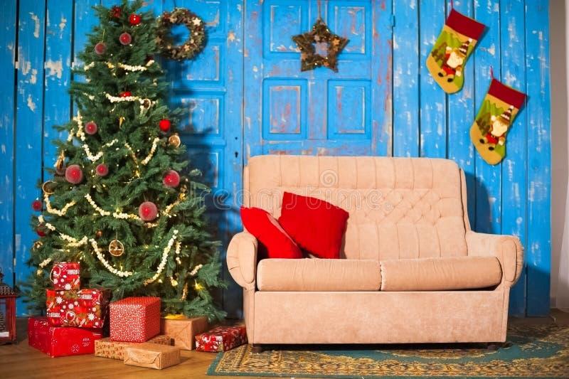 Sofà beige con i cuscini rossi contro lo sfondo di vecchie porte blu nella stanza del ` s del nuovo anno decorata Albero di Natal fotografia stock