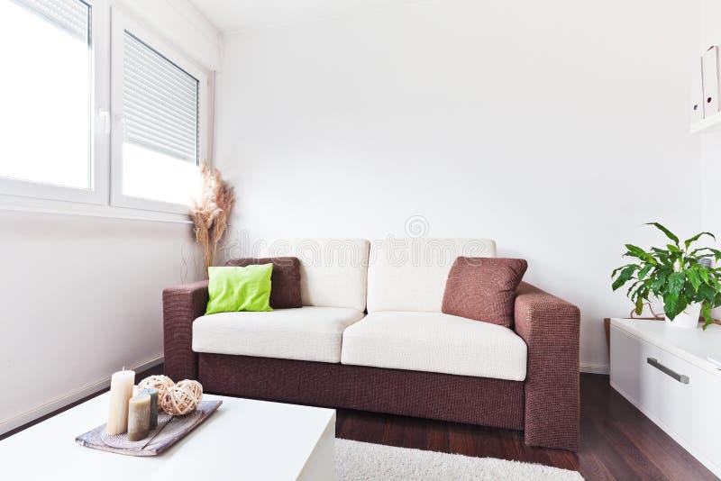 Sofà bianco e marrone del tessuto nel salone immagini stock