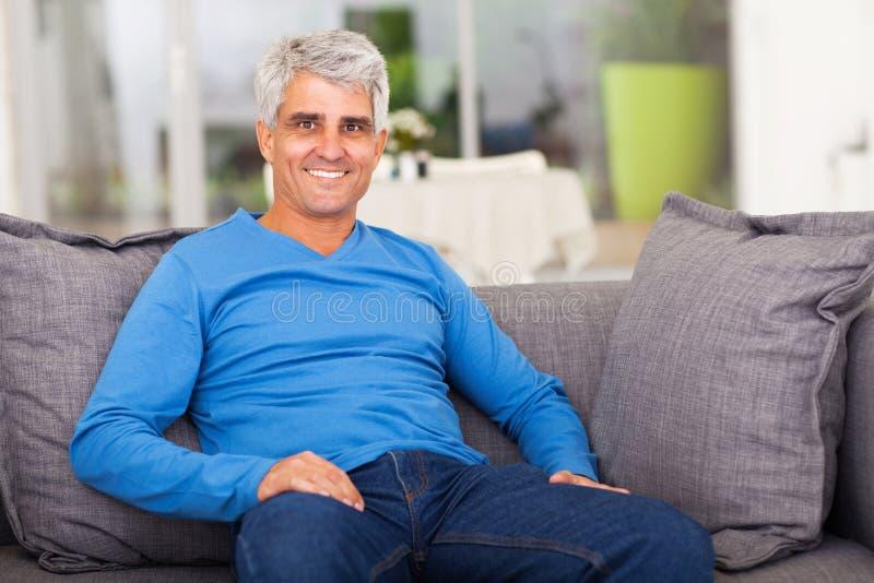 Sofà dell'uomo invecchiato mezzo fotografie stock