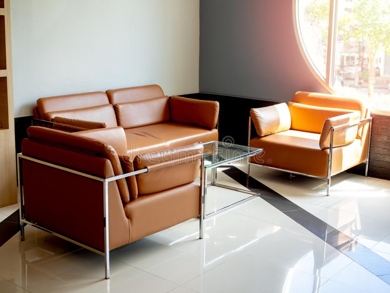 Sofà di cuoio arancio moderno messo con la tavola di vetro su fondo blu con la finestra rotonda immagini stock libere da diritti