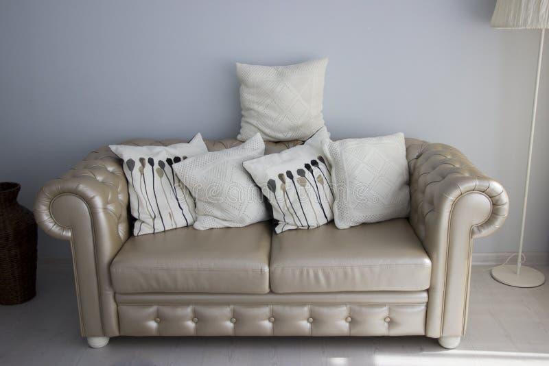 Sofà di cuoio crema Interno con mobilia Cuscini di tela sul sofà di cuoio immagini stock libere da diritti
