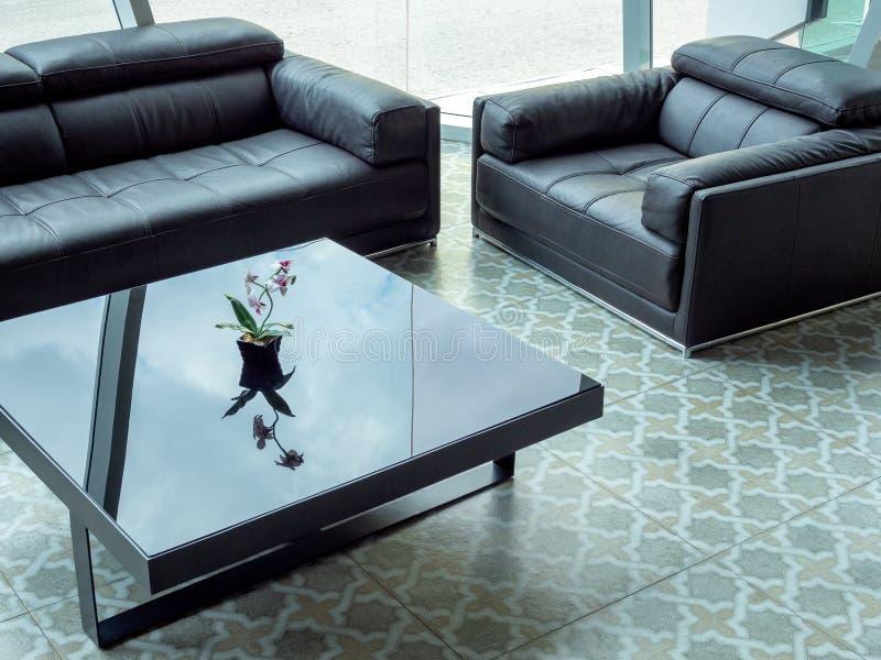 Sofà di cuoio nero moderno e tavola di vetro nera sulla pavimentazione delle mattonelle nel salone immagine stock libera da diritti