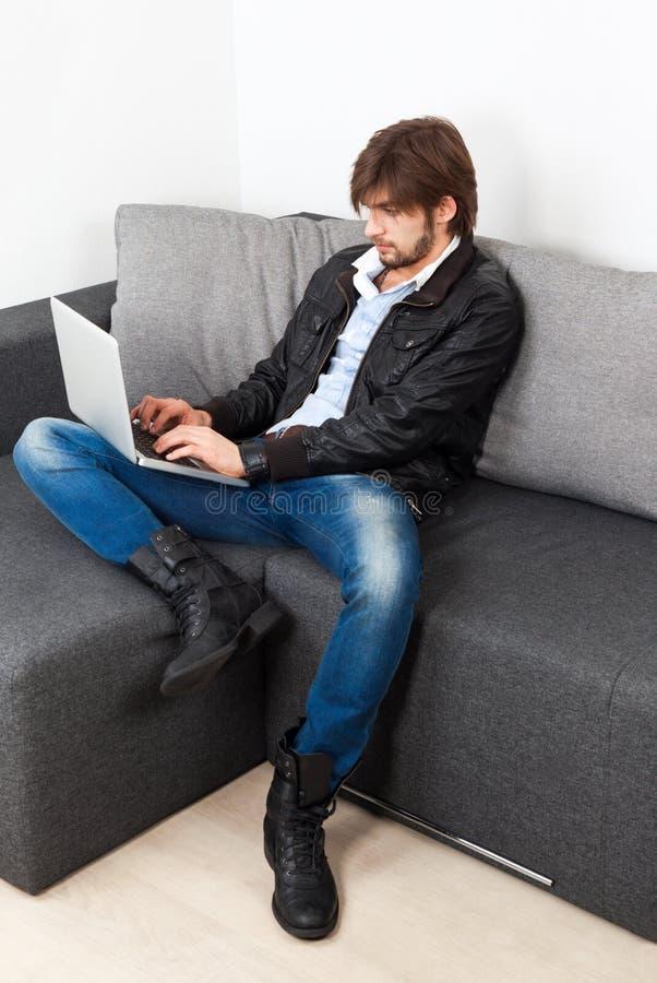 Sofà di seduta del computer portatile dei pantaloni a vita bassa dell'uomo di modo immagini stock