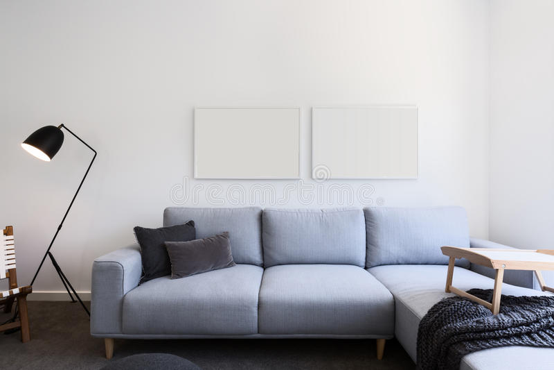 Sofà di tela blu-chiaro ed immagini in bianco in un salone immagini stock