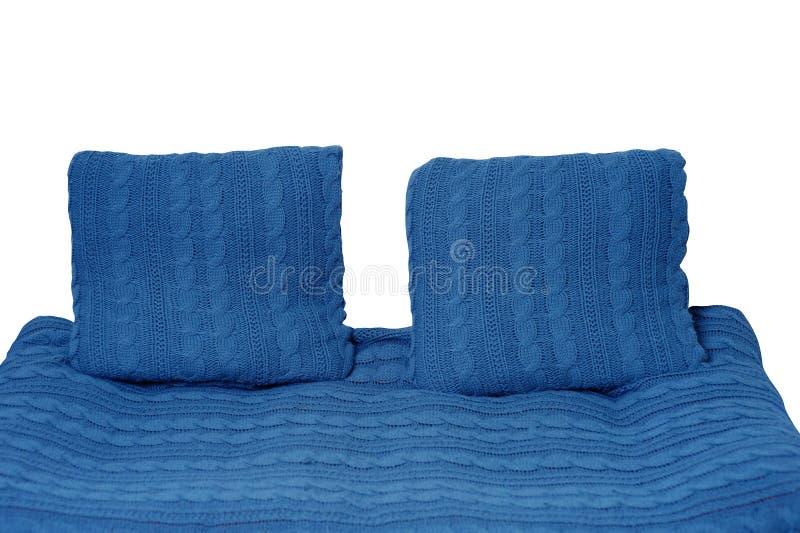 Sofà e due cuscini in blu isolato su fondo bianco immagine stock