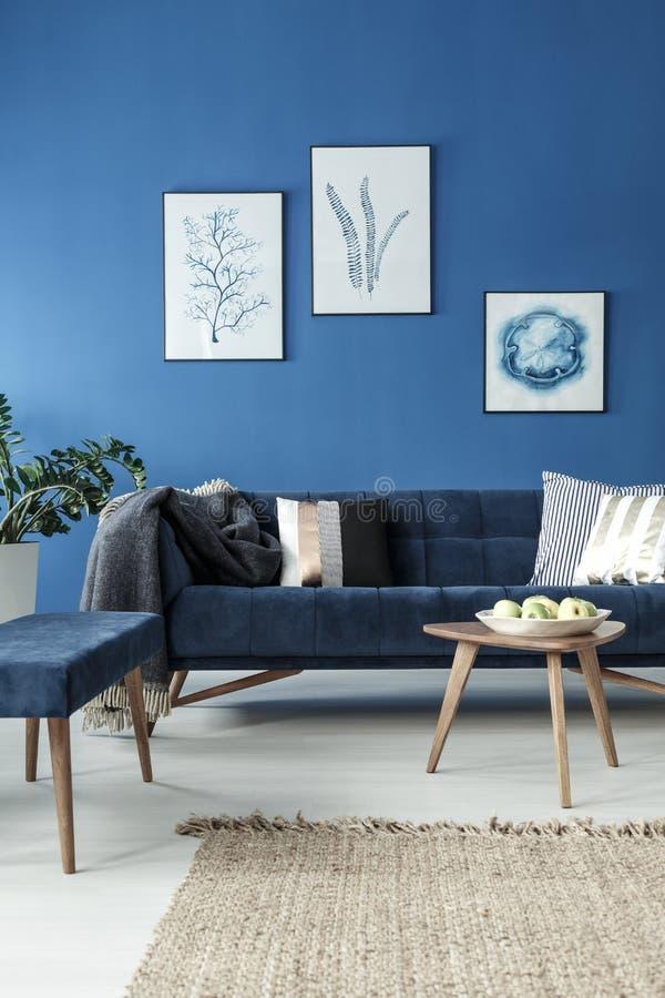 Sofà e tavola di estremità nella stanza blu fotografie stock