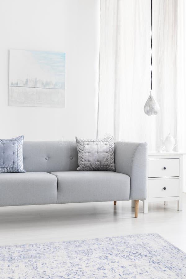 Sofà grigio con i cuscini vicino alla lampada nell'interno minimo del salone con il manifesto ed il tappeto Foto reale fotografia stock
