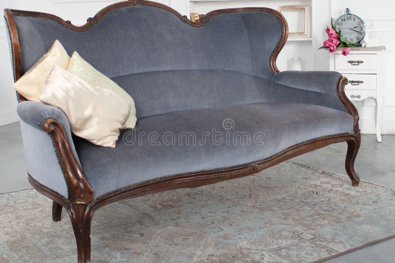 Sofà grigio d'annata con i cuscini beige, orologio con i fiori fotografia stock