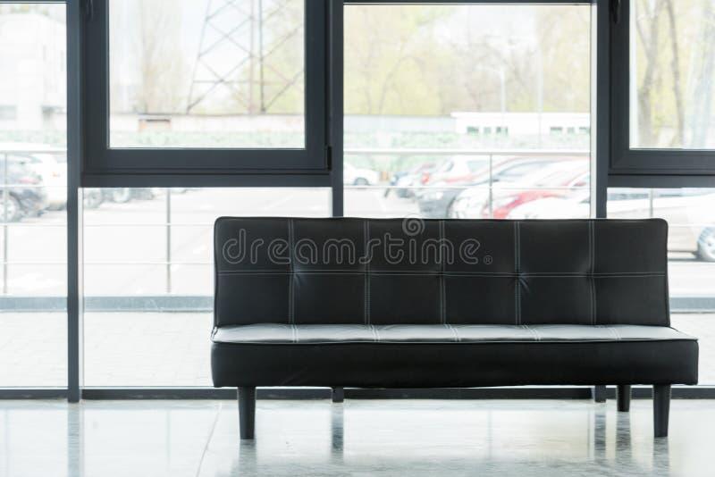 sofà nero di cuoio in vuoto immagine stock