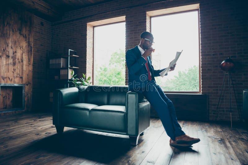 Sofà pendente dell'ufficio del tipo macho scuro della pelle che beve bevanda calda che legge il costume elegante di usura fresca  fotografia stock