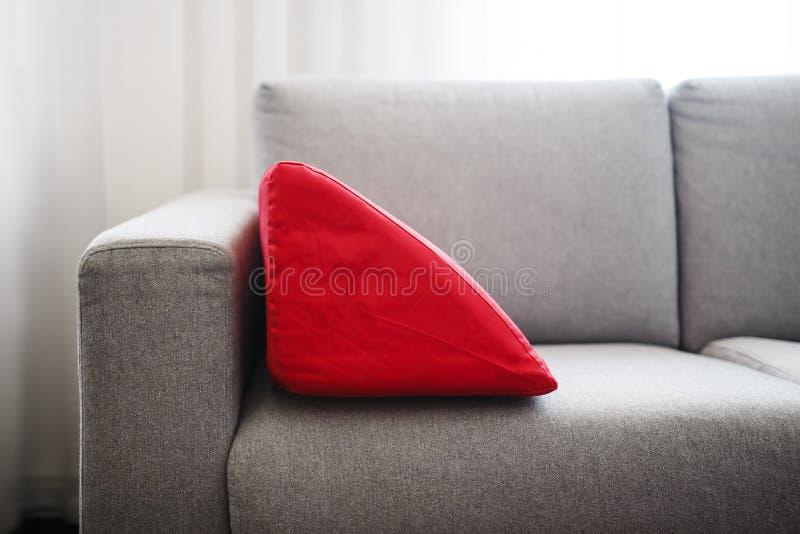 Sofá acogedor con la almohada roja en el apartamento brillante imagen de archivo