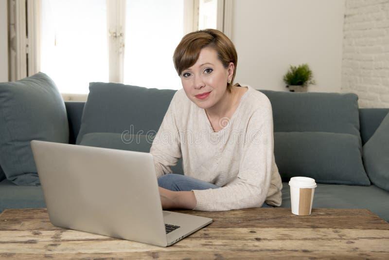 Sofá atrativo e feliz novo do sofá da mulher em casa que faz algum sorriso do trabalho do laptop relaxado no estilo de vida do em fotografia de stock royalty free