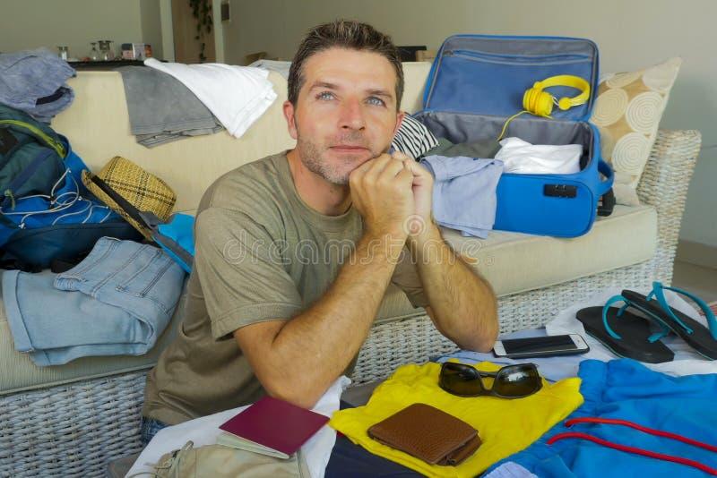 Sofá atrativo e feliz novo do homem em casa que prepara o curso para trás e roupa de dobramento da mala de viagem e que organiza  fotografia de stock royalty free