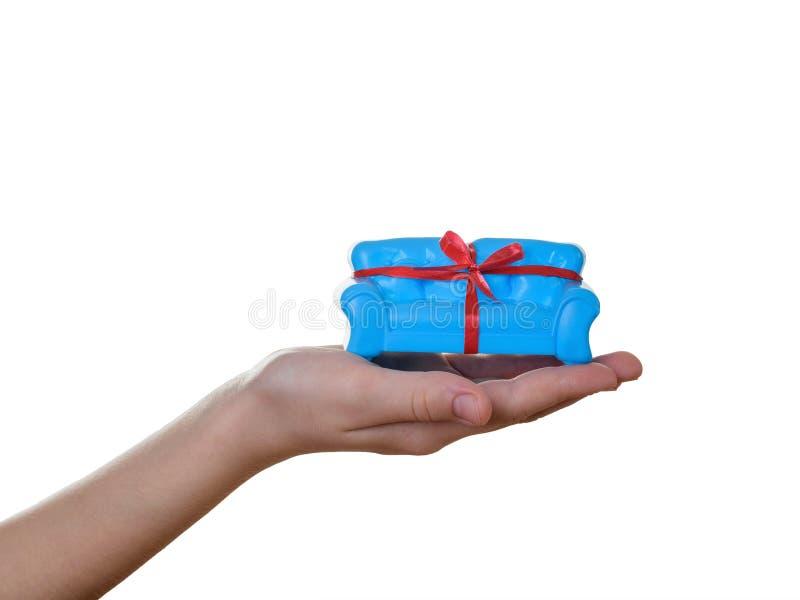 Sofá azul com a fita vermelha na mão do bebê isolada no fundo branco Presente incomum fotos de stock