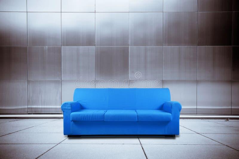 Sofá azul en fondo del metal fotos de archivo