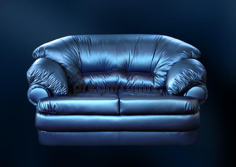 Sofá azul en un negro fotos de archivo libres de regalías