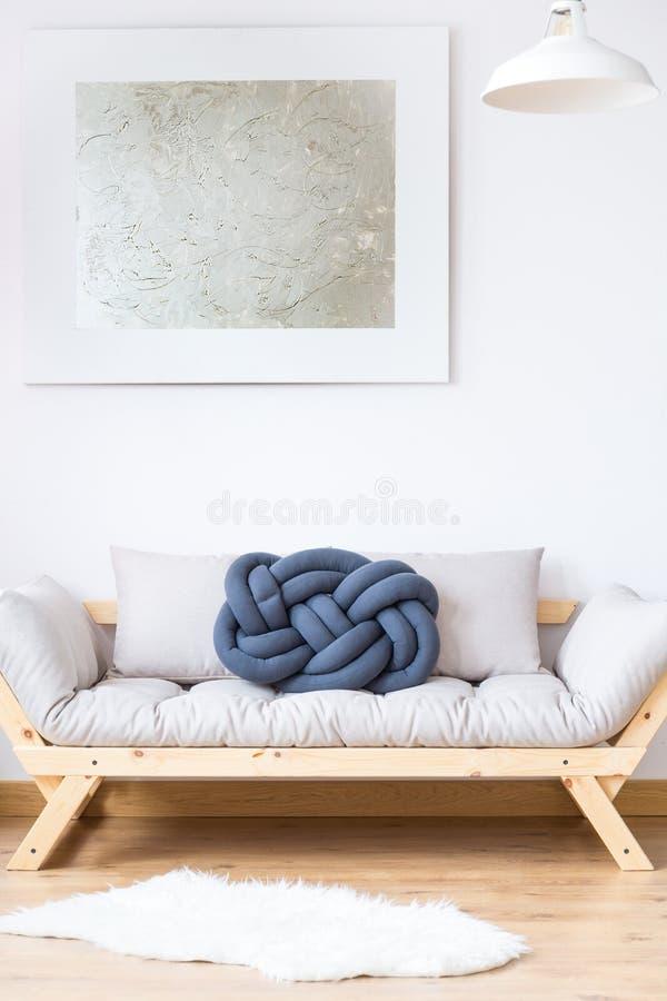 Sofá beige con la almohada azul imagen de archivo