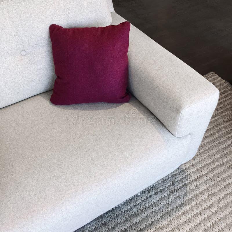 Sofá blanco con el amortiguador del rojo cereza imagenes de archivo