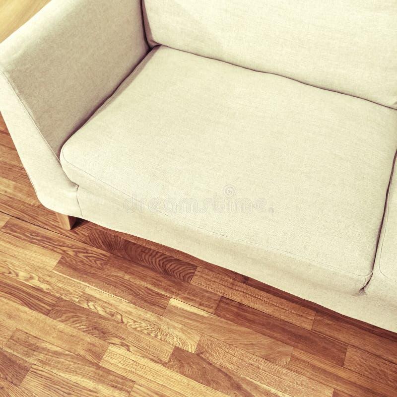 Sofá blanco simple en piso de madera imagenes de archivo