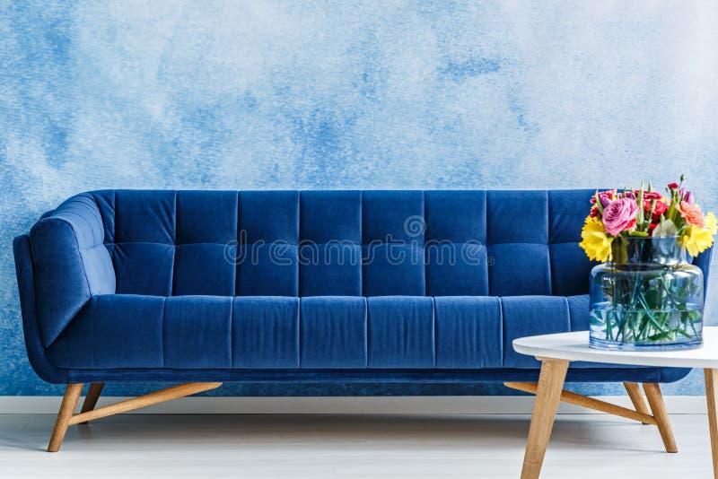 Sofá cómodo de la felpa de los azules marinos y flores coloridas en un florero imagen de archivo libre de regalías