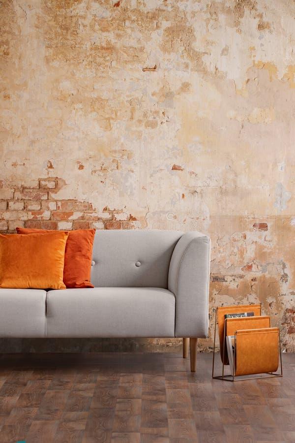 Sofá cinzento contra a parede de tijolo vermelho no interior moderno da sala de visitas Foto real foto de stock royalty free