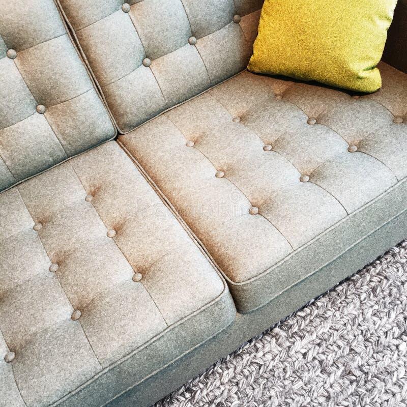 Sofá cinzento de matéria têxtil com coxim fotos de stock royalty free