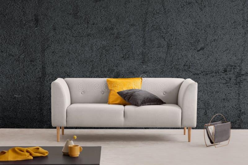 Sofá cinzento no interior da sala de visitas com parede e a tabela textured Foto real fotografia de stock