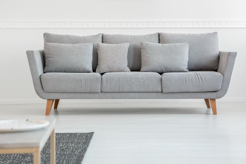 Sofá cinzento simples no interior escandinavo brilhante da sala de visitas imagens de stock
