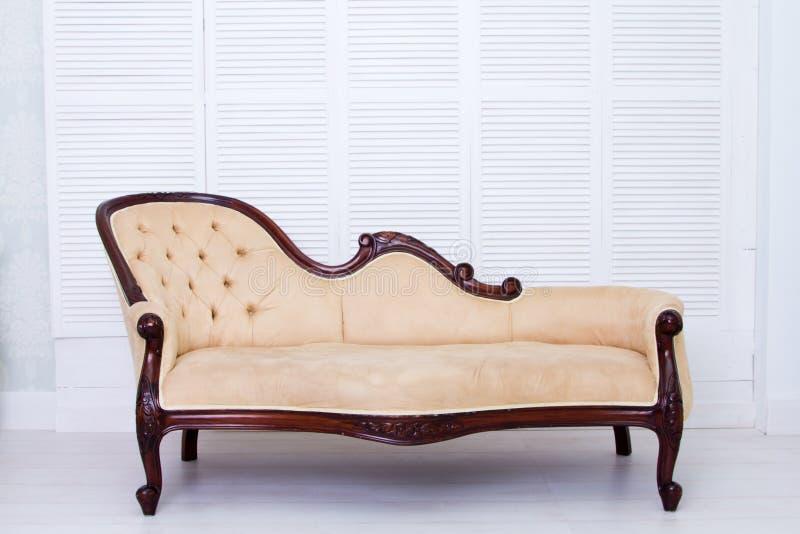 Sofá clásico del estilo de la materia textil beige en sitio del vintage imagenes de archivo