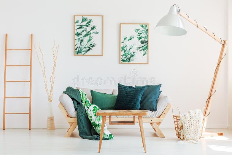 Sofá con la manta floral verde fotos de archivo