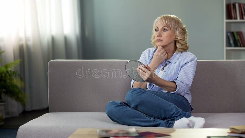Sofá de assento da senhora superior pensativa com espelho de mão, problemas de envelhecimento, skincare fotografia de stock
