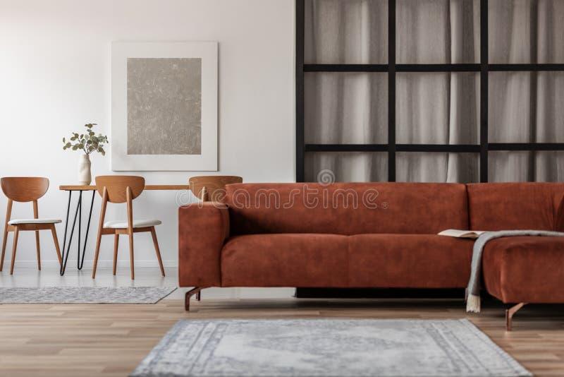 Sofá de canto elegante em apartamento de estúdio em espaço aberto com espaço para jantar e viver fotos de stock royalty free