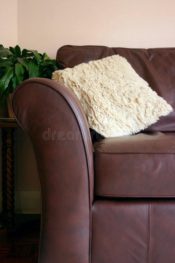 Sofá de couro de Brown com coxim foto de stock