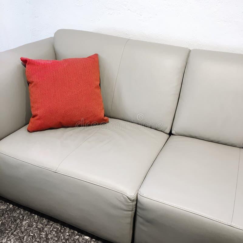 Sofá de couro simples com coxim vermelho fotografia de stock
