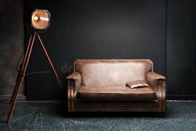 Sofá de cuero de Brown en interior oscuro del desván Pared pintada negra del cemento con la lámpara retra Foto del fondo con el e fotos de archivo