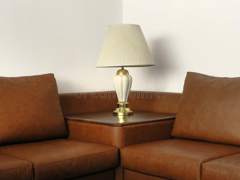 Sofá de cuero con la lámpara de escritorio imagen de archivo