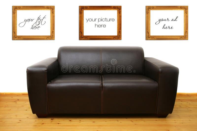 Sofá de cuero de Brown y marcos en blanco de la foto foto de archivo