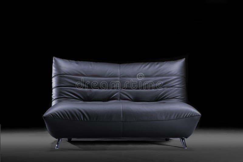 Sofá de cuero de moda en un fondo negro foto de archivo