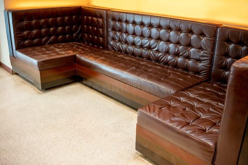 Sofá de cuero marrón clásico del vintage en el piso blanco contra amarillo fotos de archivo libres de regalías