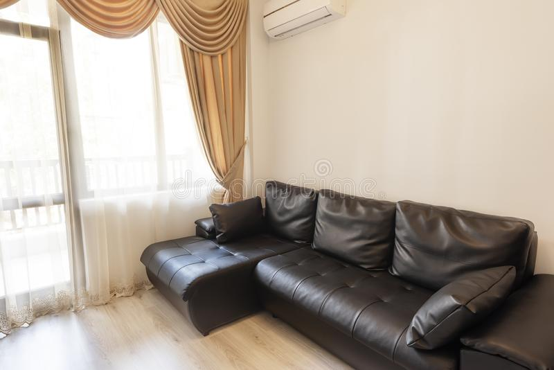 Sofá de cuero negro cerca de una ventana grande con esquileos, cortinas y pañerías Muebles clásicos de la sala de estar fotografía de archivo