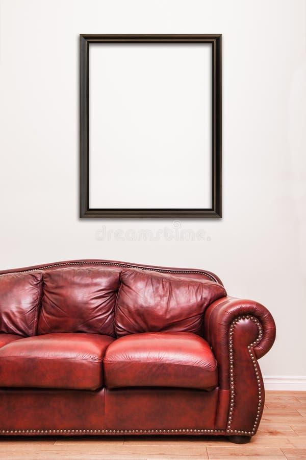 Sofá de cuero rojo lujoso delante de una pared en blanco foto de archivo