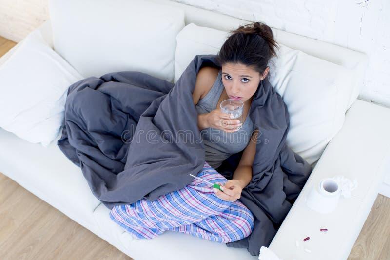 Sofá de encontro do doente da mulher latino-americano atrativa nova em casa no frio e na gripe no sintoma da doença da queixa imagem de stock royalty free