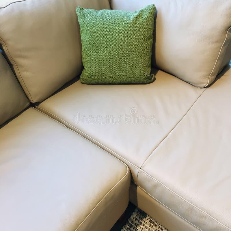 Sofá de la esquina gris con el amortiguador verde fotos de archivo