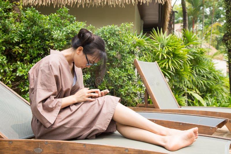 Sofá de la mujer y teléfonos elegantes del juego foto de archivo
