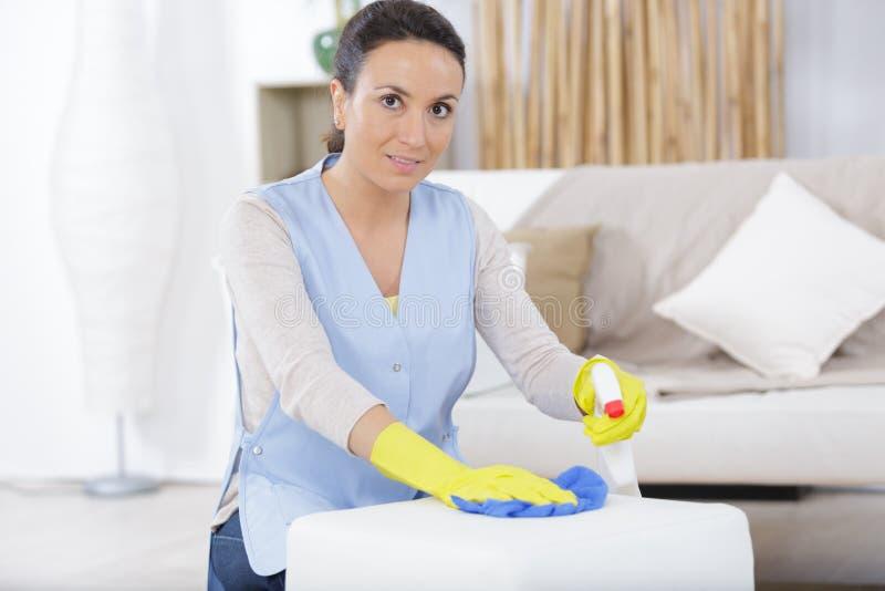 Sofá de limpieza de la mujer en casa fotos de archivo
