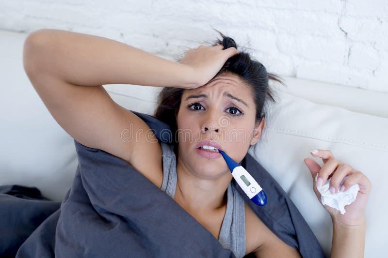 Sofá de mentira del enfermo de la mujer hispánica atractiva joven en casa en frío y gripe en síntoma de la enfermedad de la queja imagenes de archivo