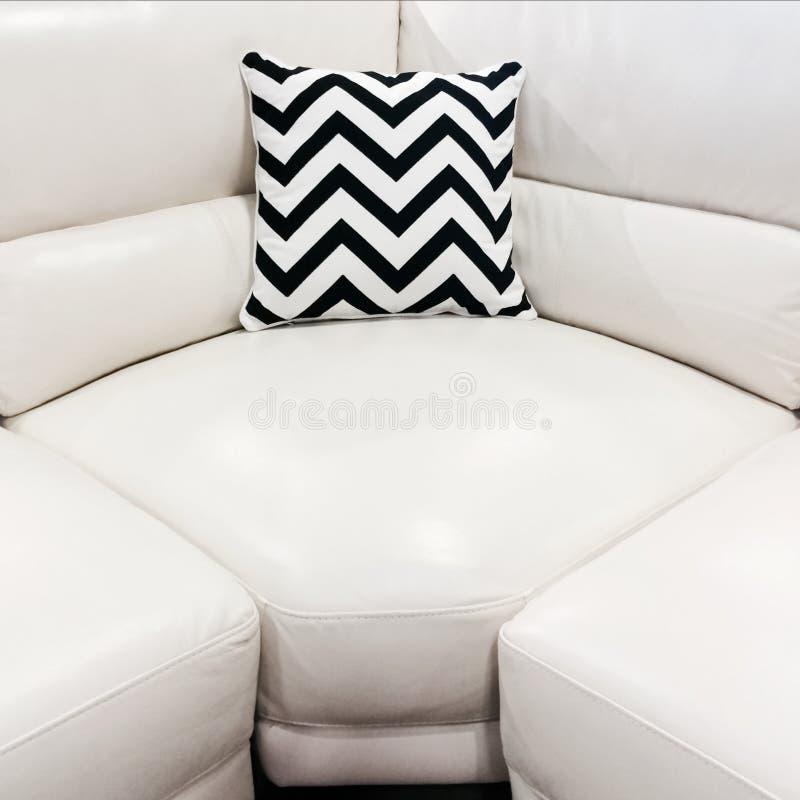 Sofá del cuero blanco con el amortiguador decorativo imagen de archivo libre de regalías